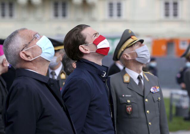 Em Viena, o presidente da Áustria, Alexander Van Der Bellen (à esquerda), o chanceler austríaco, Sebastian Kurz (centro), usam máscaras durantes comemorações de um feriado nacional, em 26 de outubro de 2020