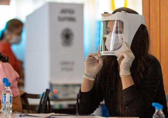 Em Curitiba, uma mesária usa máscara, proteção facial e luvas para proteger-se da COVID-19 durante a votação nas eleições municipais, em 15 de novembro de 2020