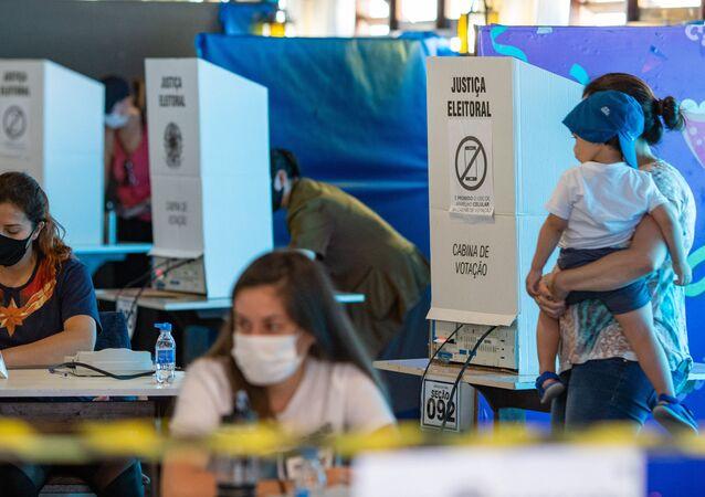 Em Curitiba, no clube Duque de Caxias, eleitores e mesários são vistos usando máscaras contra a COVID-19 durante as eleições municipais de 2020, em 15 de novembro de 2020