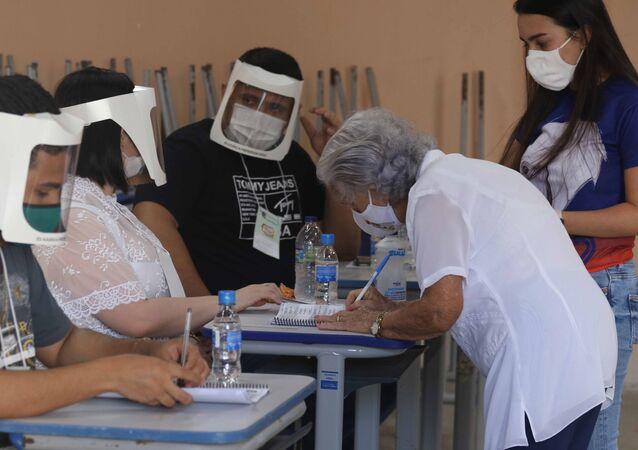 Perto da capital cearense, Fortaleza, uma mulher idosa, usando máscara, vota acompanhada nas eleições municipais de 2020 na cidade de Russas, em meio à pandemia da COVID-19, em 15 de novembro de 2020
