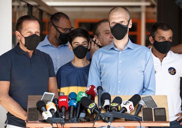 Em São Paulo, o prefeito e candidato à reeleição, Bruno Covas (PSDB) (à frente, à direita), fala ao lado do governador paulista, João Doria (PSDB) (à frente, à esquerda), em frente à zona eleitoral escola Vera Cruz, em 15 de novembro de 2020. Ambos usam máscara contra a COVID-19