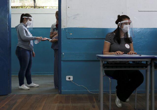 Mulher desinfeta a mão em zona eleitoral em São Bernardo do Campo, em São Paulo
