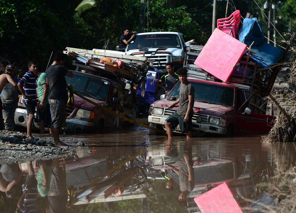 Trabalhadores em estrada inundada durante evacuação por causa do furacão Iota, El Progreso, Honduras.