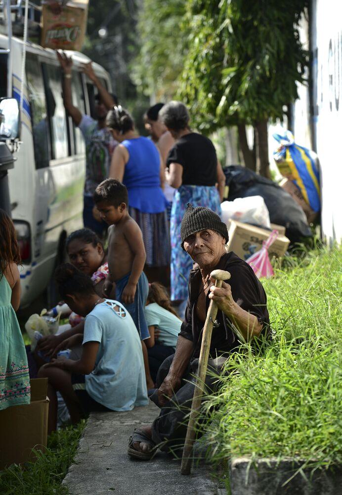 Pessoas esperam para ser evacuadas de campos de banana a bordo de um miniônibus no município de La Lima, Honduras.