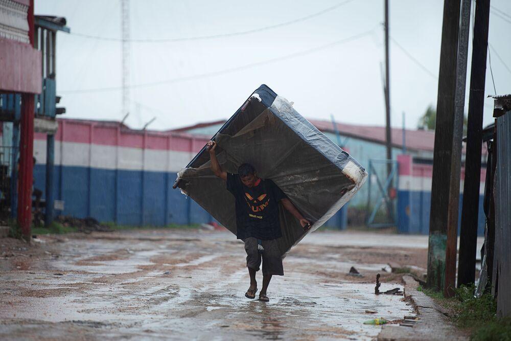 Homem carrega colchão para abrigo enquanto o furacão Iota se aproxima de Puerto Cabezas, Nicarágua, 16 de novembro 2020.