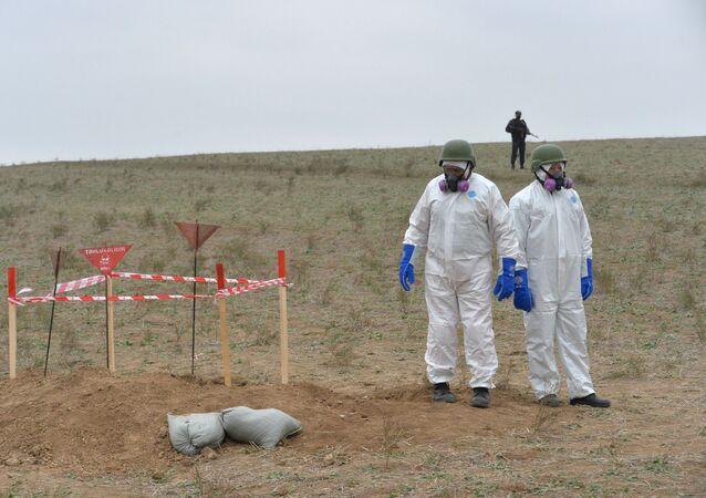Funcionários da Agência Nacional de Desminagem de Territórios do Azerbaijão (ANAMA) durante a preparação para destruição de uma munição de fósforo no distrito de Fizuli, Azerbaijão.