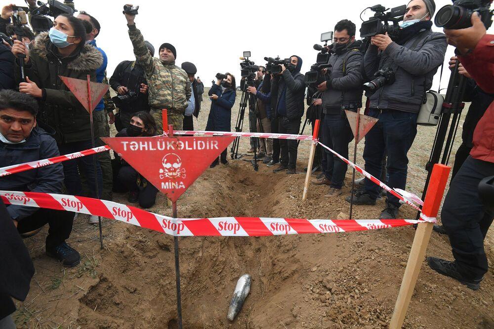 Jornalistas fazem a cobertura do trabalho dos funcionários da Agência Nacional de Desminagem de Territórios do Azerbaijão (ANAMA).