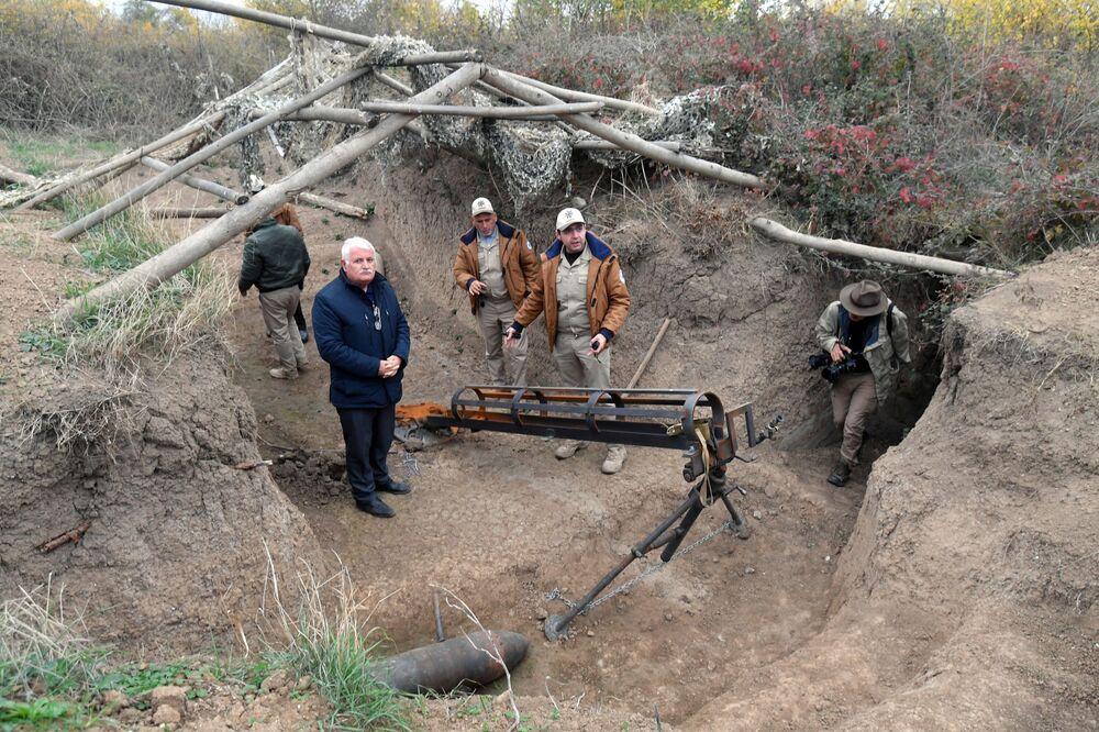Funcionários da Agência Nacional de Desminagem de Territórios do Azerbaijão examinam lançador improvisado de projéteis, abandonado no distrito de Fizuli, Azerbaijão.
