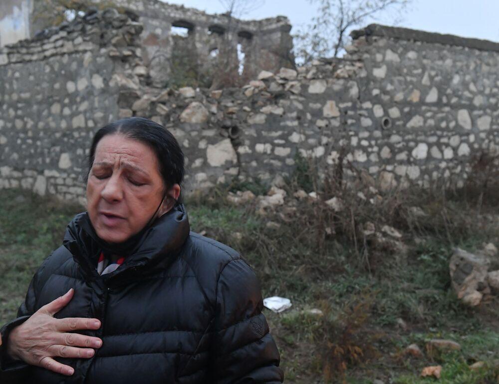 Mulher ao lado das ruínas de sua casa em Fizuli, abandonada em 1994.