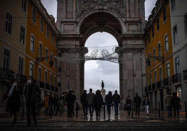 Transeuntes caminham pela rua Augusta, no centro de Lisboa, enquanto governo português debate medidas contra a pandemia de coronavírus