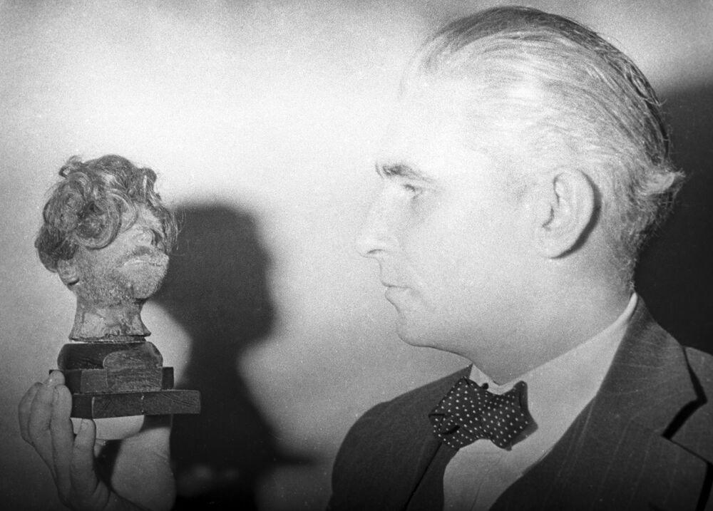 Representante do tribunal militar norte-americano nos julgamentos de Nuremberg Thomas Dodd com uma cabeça humana dissecada