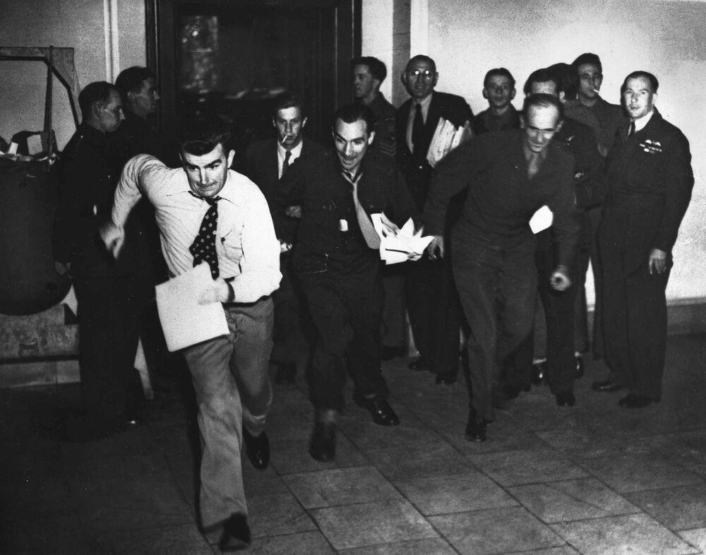 Repórteres militares correm para o telefone em 1º de outubro de 1946 para informar das notícias sobre o veredicto do Julgamento da História