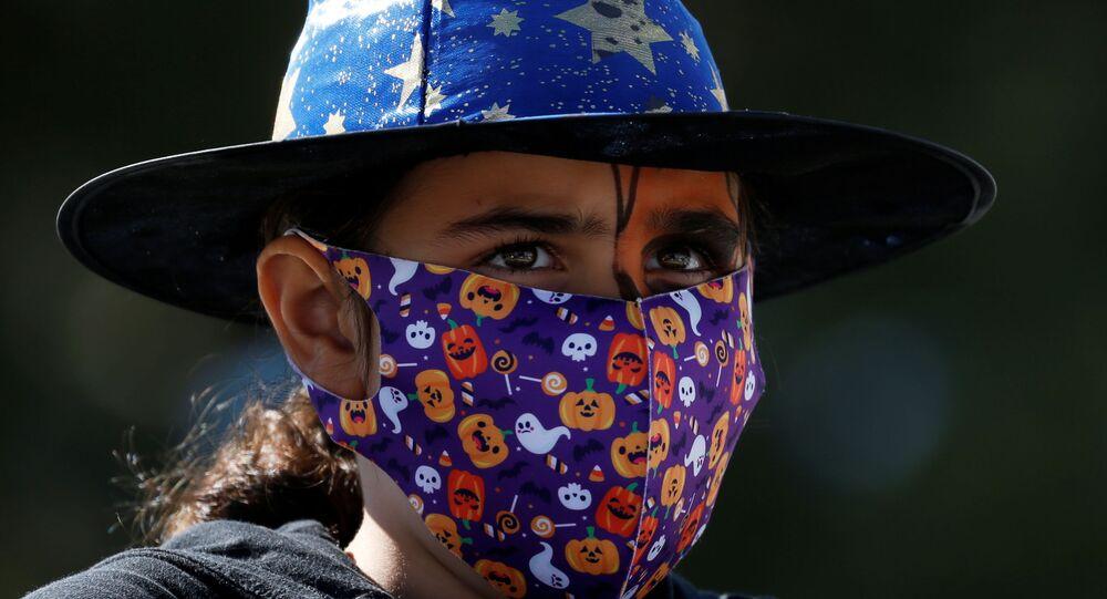 Menina usa máscara e um chapéu de bruxa enquanto assiste a um show temático de Halloween para crianças durante a pandemia de COVID-19, em Ta' Qali, Malta, 1º de novembro de 2020