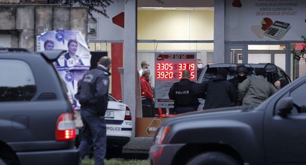 Policiais se reúnem em uma rua perto de um escritório de uma organização de microfinanciamento, depois que um homem não identificado fez reféns em Tbilisi, capital da Geórgia