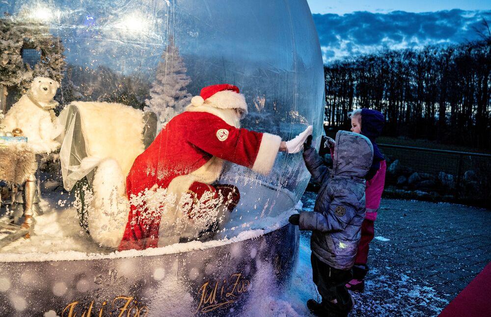 Papai Noel fala com crianças em uma bolha gigante no zoológico em Aalborg, Dinamarca