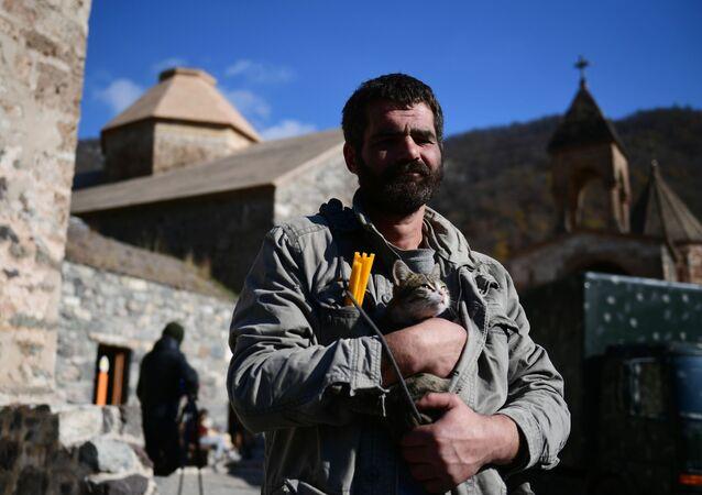 Homem segura um gato perto de um templo no mosteiro de Dadivank em Nagorno-Karabakh