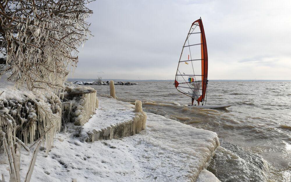 Praticante de windsurf Aleksandr Orlov põe fim à temporada em um reservatório de água, em Novossibirsk