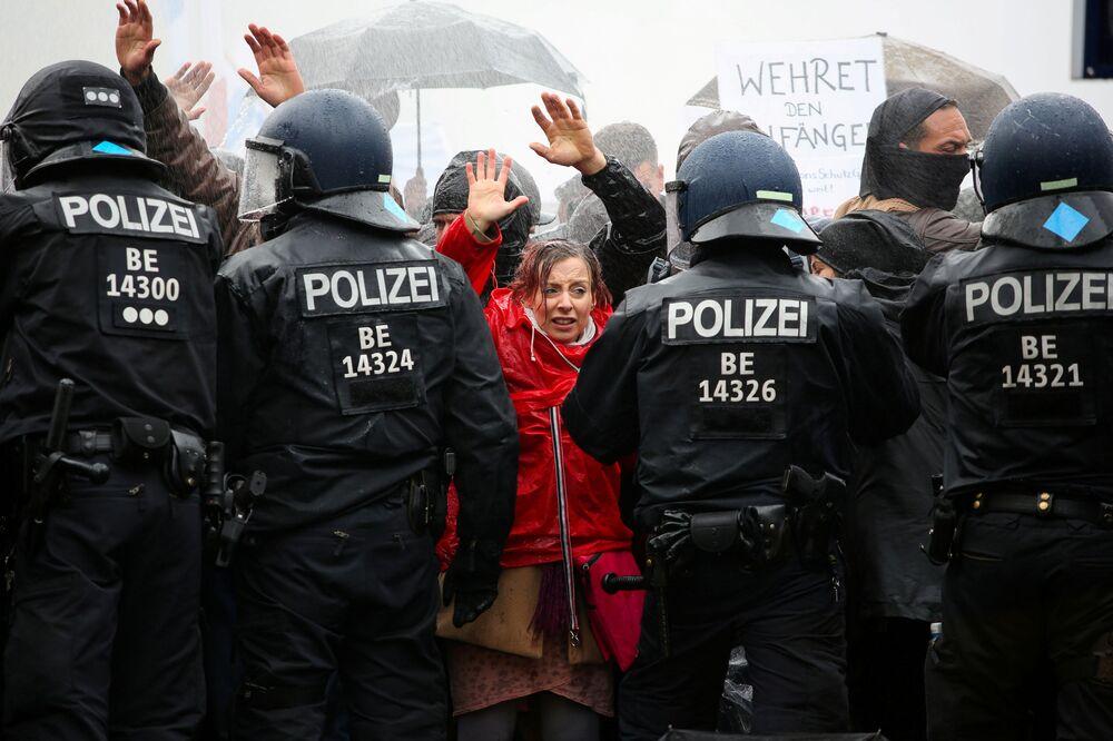 Manifestantes em frente a cordão policial durante um protesto contra as restrições governamentais associadas com o novo coronavírus, em Berlim, Alemanha