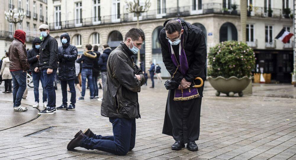 Um crente faz confissão perante um sacerdote em plena rua em Nantes, França