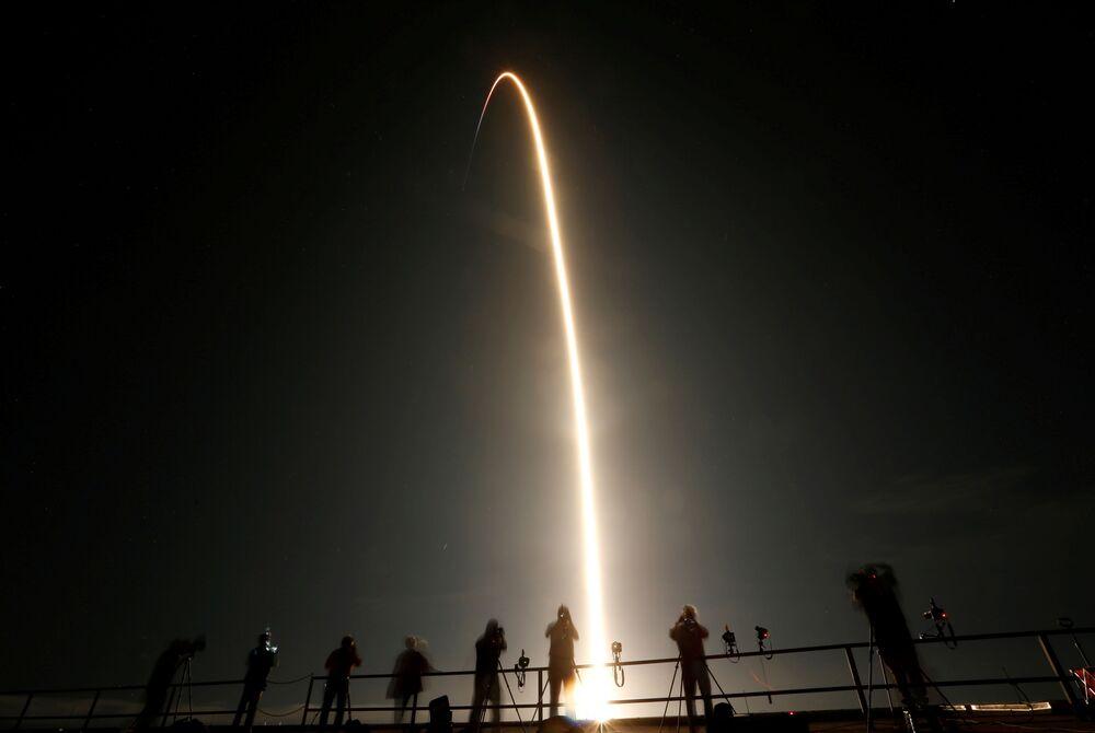 Pessoas assistem o lançamento de foguete SpaceX Falcon 9 que transporta uma cápsula Crew Dragon com quatro astronautas a bordo