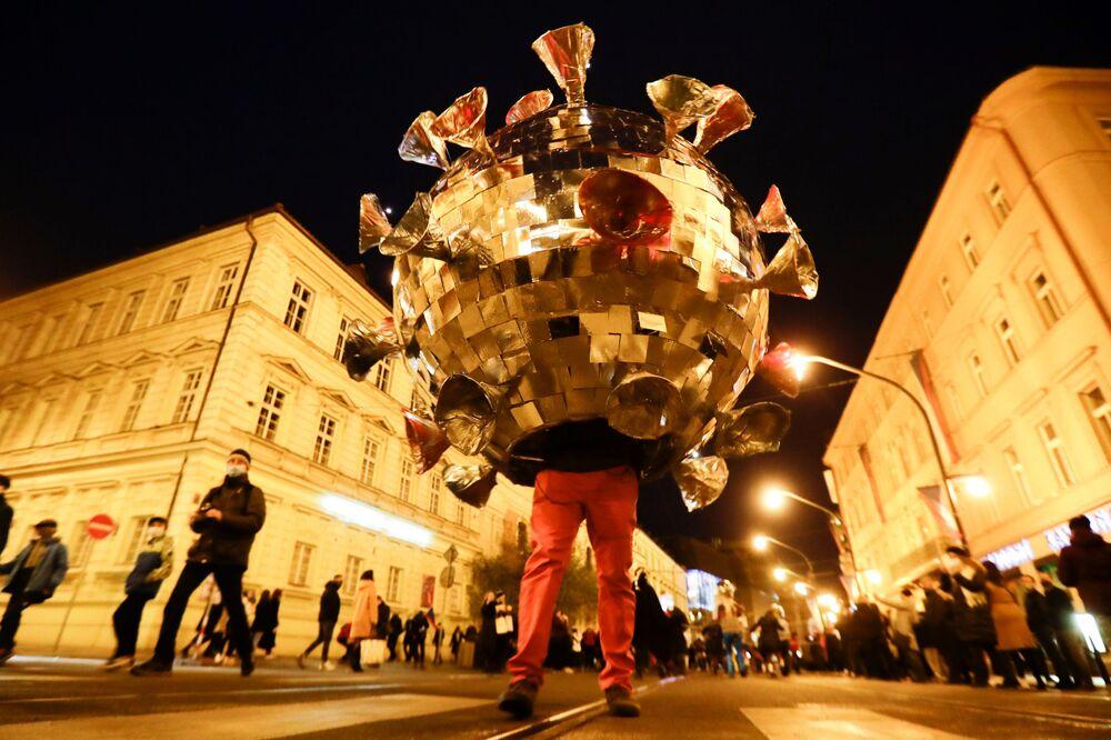 Homem usando traje de COVID-19 protesta contra as restrições por causa do novo coronavírus em Praga, República Tcheca