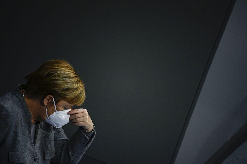 Chanceler alemã Angela Merkel ajusta sua máscara durante uma reunião no Bundestag (Parlamento da Alemanha)