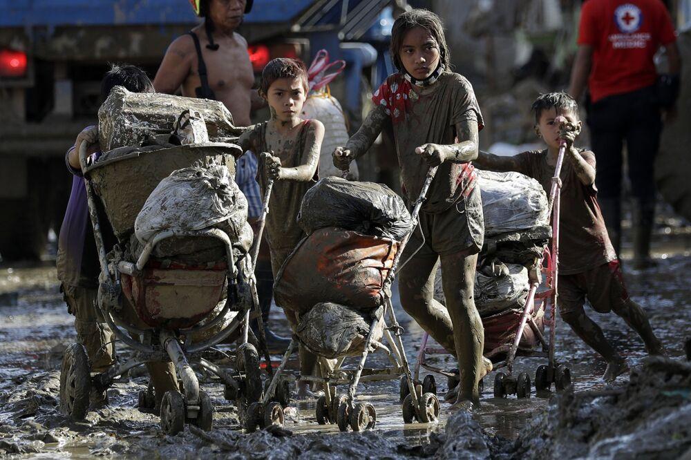 Crianças transportando carrinhos com seus pertences em uma povoação afetada pelo tufão Vamco nas Filipinas