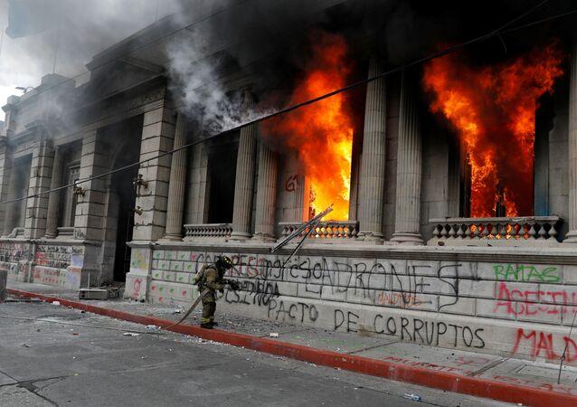 Bombeiro tenta apagar as chamas do edifício do Congresso Nacional na Guatemala