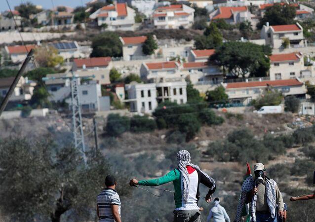 Na Faixa de Gaza, manifestantes palestinos protestam em frente a um assentamento judeu, em Kafr Qaddum, área ocupada por Israel na região, em 13 de novembro de 2020