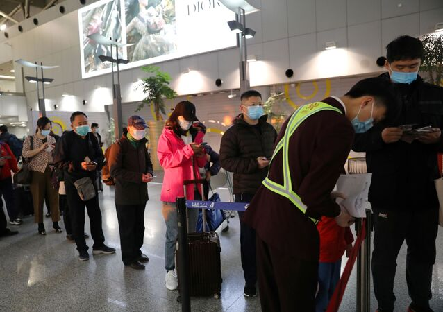 Passageiros e funcionários com máscaras contra coronavírus em aeroporto da China