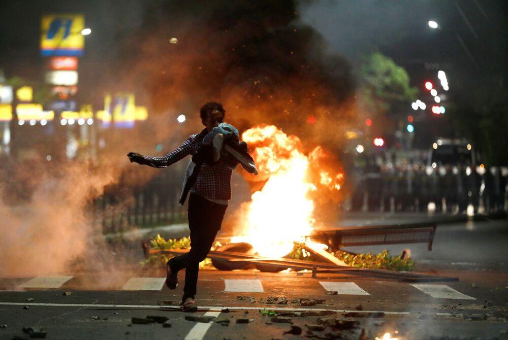 Manifestante corre durante protesto contra o racismo, depois de João Alberto Silveira Freitas ter sido morto por seguranças brancos em unidade do supermercado Carrefour em Porto Alegre, 23 de novembro, 2020.