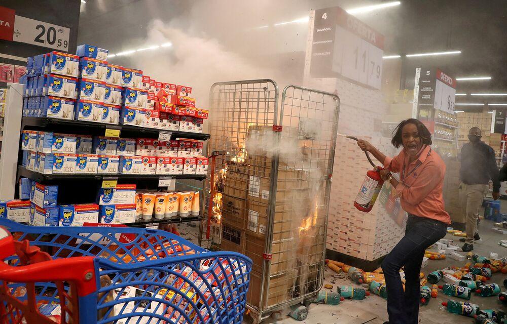 Mulher apaga fogo em loja vandalizada do supermercado Carrefour durante uma marcha em São Paulo pelo Dia da Consciência Negra e pela morte de João Alberto Silveira Freitas, homem negro que foi espancado até a morte no supermercado em Porto Alegre, 20 de novembro, 2020.