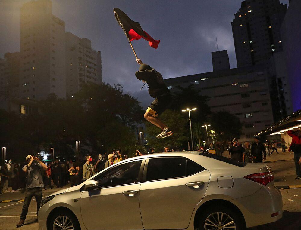 Manifestante salta por cima do carro durante uma marcha em São Paulo no Dia da Consciência Negra em protesto contra a morte de João Alberto Silveira Freitas, homem negro espancado até ser morto em um supermercado em Porto Alegre, 20 de novembro, 2020.