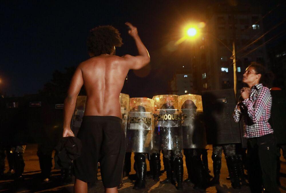 Homem negro confronta tropa de choque enquanto uma mulher negra reza durante protesto contra a morte de João Alberto Silveira Freitas, na quinta-feira (19), quando desencadeou no Brasil uma onda de indignação.