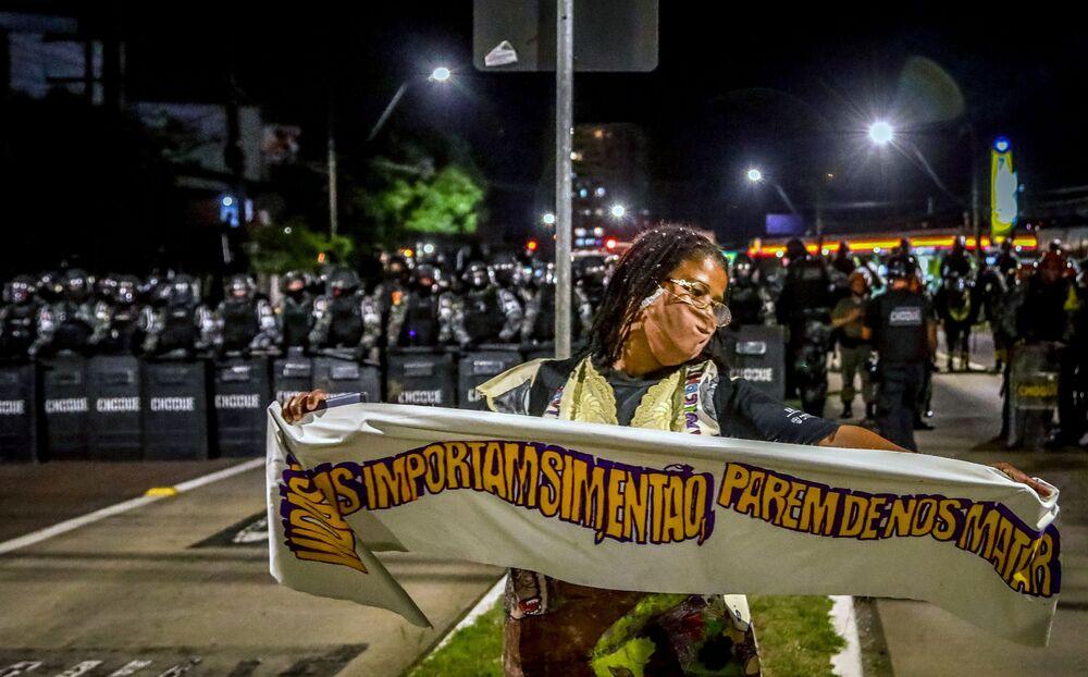 Mulher negra segura uma faixa em frente a tropa de choque durante o protesto contra a morte de João Alberto Silveira Freitas, após o mesmo ter sido morto por seguranças brancos no supermercado Carrefour em Porto Alegre, 23 de novembro, 2020.