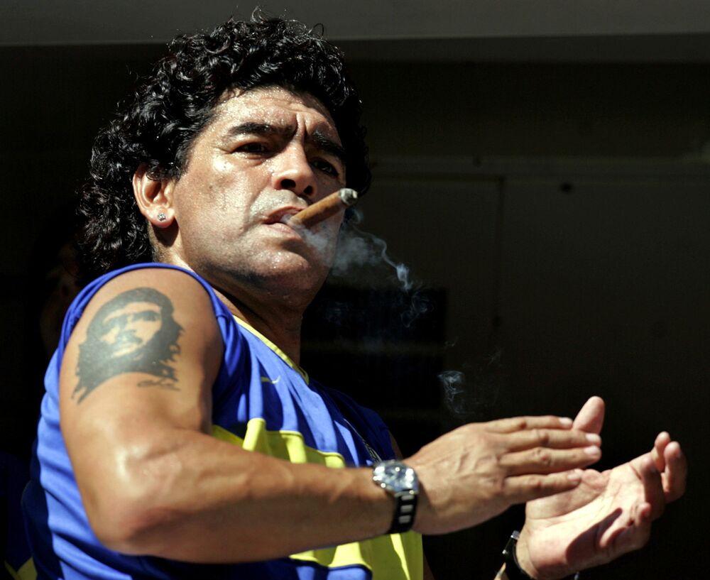 Diego Maradona fuma um charuto enquanto assiste ao início da partida entre Boca Juniors e San Lorenzo no estádio de La Bombonera, em Buenos Aires, em 19 de fevereiro de 2006