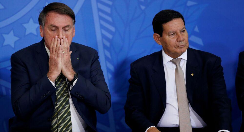 Jair Bolsonaro, gesticula perto do vice-presidente do Brasil, Hamilton Mourão, durante cerimônia de posse do novo ministro da Justiça, André Luiz de Almeida Mendonça.