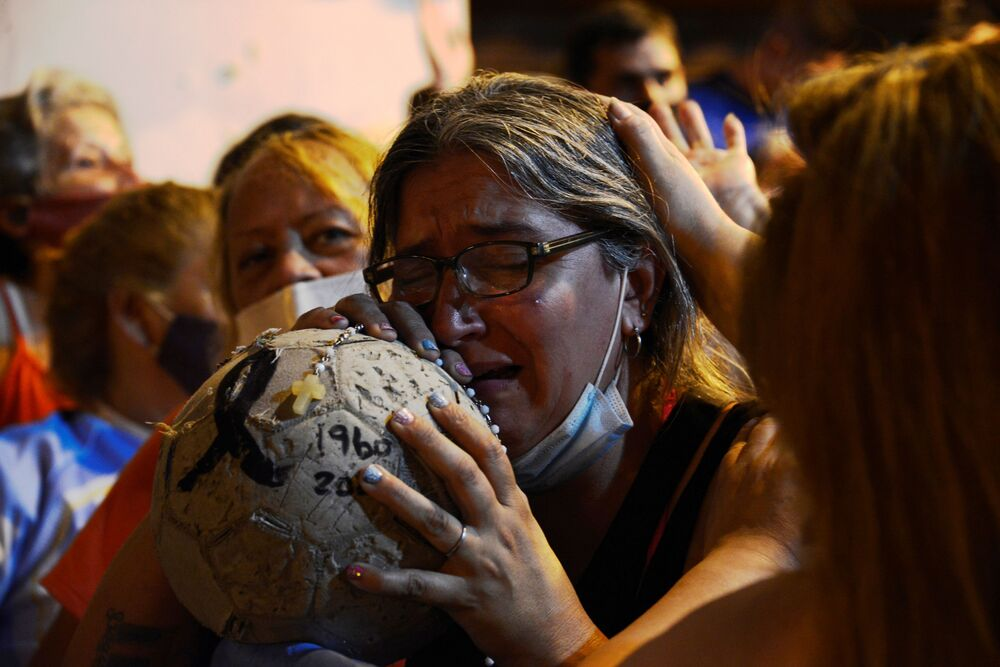 Mulher chora com uma bola de futebol, após a morte Diego Maradona na Argentina.