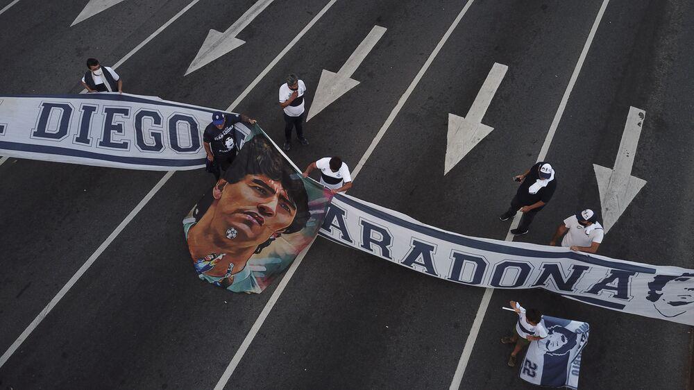 Fãs com faixa durante o luto pela morte de Diego Maradona.