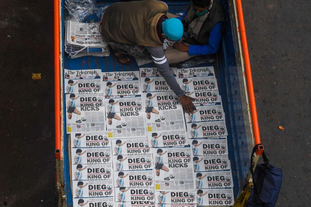 Venda de jornais na Índia com capas sobre a morte de Diego Maradona.