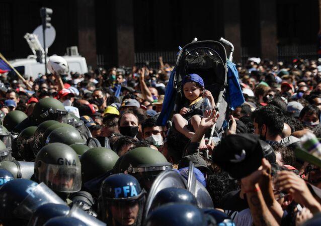 Em Buenos Aires, uma criança em um carrinho de bebê é erguida acima da multidão que acompanha o velório do ex-jogador argentino Diego Armando Maradona, na Casa Rosada, em 26 de novembro de 2020