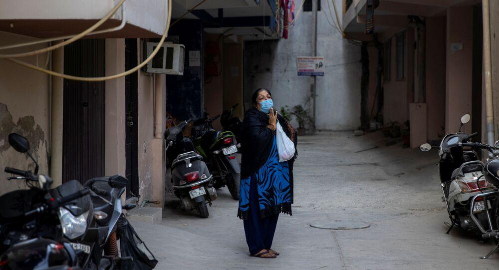Esposa de uma vítima da doença do novo coronavírus (COVID-19) chora olhando para o corpo de seu marido sendo levado para cremação em Nova Deli, Índia, 26 de novembro de 2020
