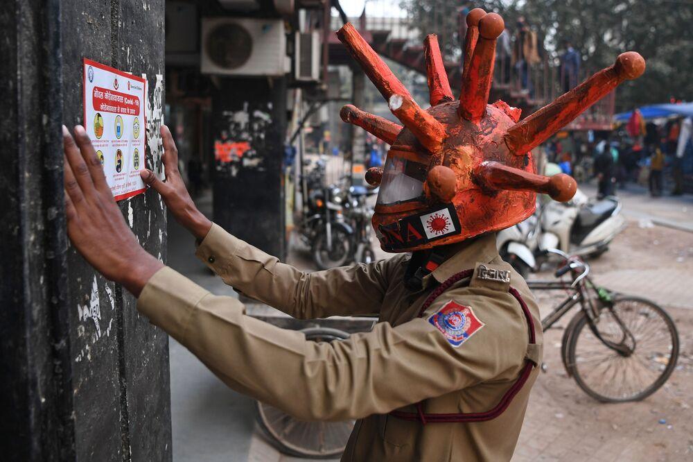Voluntário com máscara temática do coronavírus exibe cartaz informativo em mercado de Nova Deli, na Índia