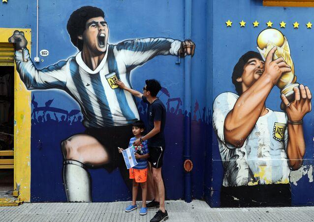 Homem e criança diante de grafites do ídolo do futebol Diego Maradona em Bueno Aires