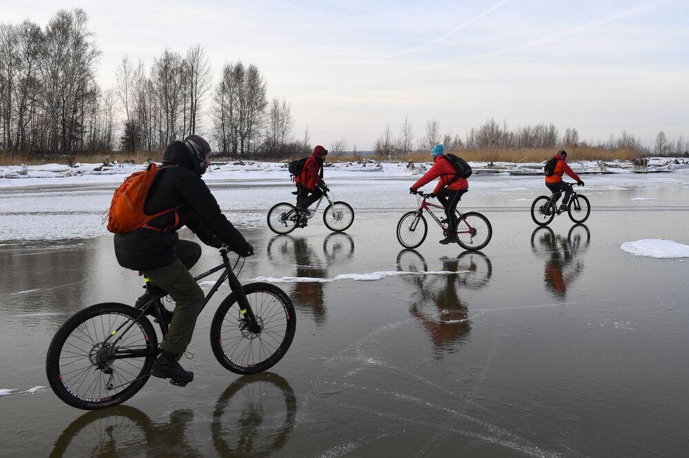 Ciclistas pedalam em reservatório congelado de hidrelétrica, perto da ilha Tan-Van, na Sibéria