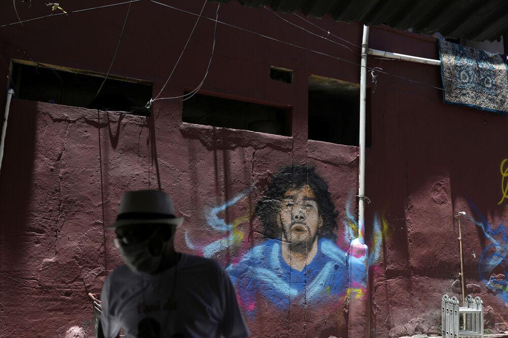 Homem com máscara para se proteger da COVID-19 diante de muro com grafite do jogador argentino Diego Maradona, no Rio de Janeiro