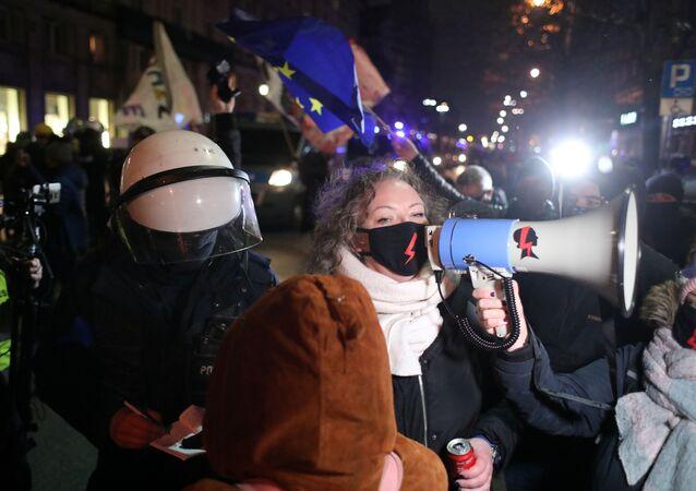 Em Varsóvia, um policial aparece atrás de Marta Lempart, liderança do movimento Strajk Kobiet (Greve das Mulheres) enquanto ela discursa durante protesto contra a proibição do aborto e em comemoração dos 102 anos do sufrágio feminino no país, em 28 de outubro de 2020