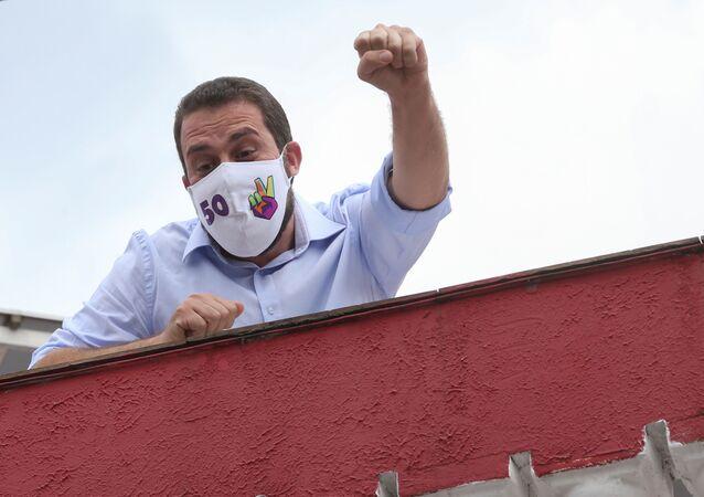 Candidato Guilherme Boulos acena para apoiadores de sua casa em São Paulo