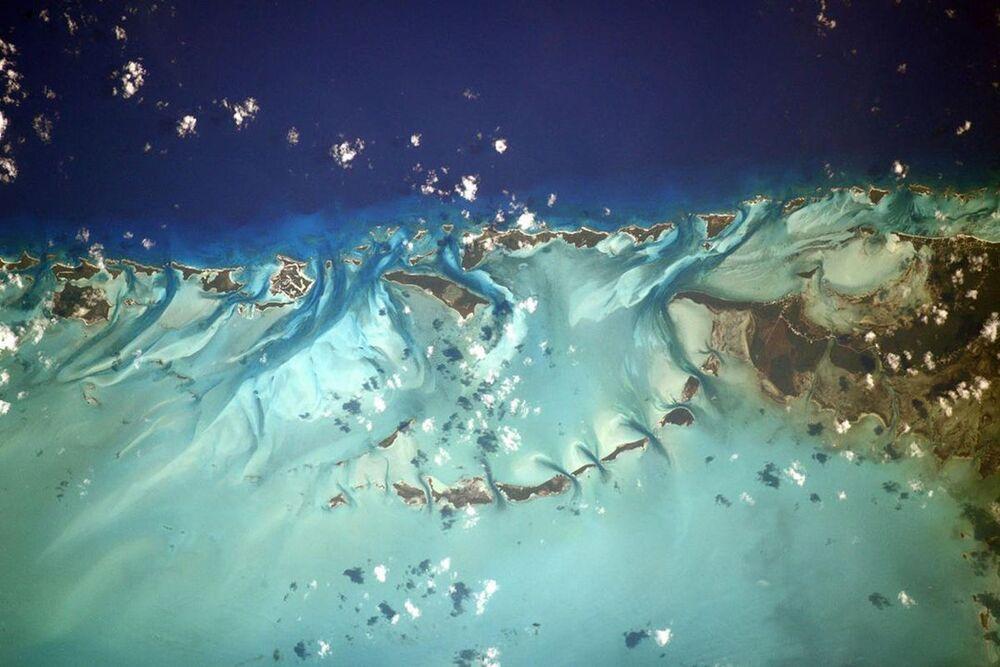 As Bahamas, localizadas entre a ilha de Cuba e península da Flórida, frequentemente imaginadas como um tipo de paraíso, sendo difícil argumentar contra essa opinião, especialmente quando vistas de uma altura de 400 quilômetros. Amigos, estas cores são incríveis: aqui há todos os tons de azul! Até parece que estão provocando desde lá com suas praias infinitas e água turquesa. Bahamas são de verdade um paraíso com praias incríveis, clima quente e vegetação exuberante. O arquipélago é composto por 700 ilhas e mais de dois mil recifes de corais. Claro que elas não cabem em uma foto. No entanto, a maioria delas são desabitadas