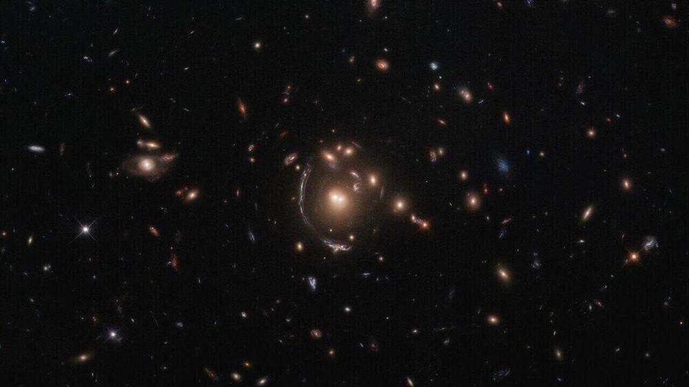Esta imagem do telescópio espacial Hubble, da NASA e Agência Espacial Europeia, mostra a galáxia LRG-3-817, também conhecida como SDSS J090122.37+181432.3. A galáxia, cuja imagem é distorcida por efeitos da lente gravitacional, aparece como um arco longo à esquerda do grupo central de galáxias. Uma consequência importante da lente gravitacional é ampliação, permitindo-nos observar objetos que de outra forma estariam demasiado longe ou seriam demasiado fracos para ser vistos. Hubble usa este efeito de ampliação para estudar objetos para lá dos que normalmente são detectáveis com a sensibilidade de seu espelho principal de 2,4 metros de diâmetro, mostrando-nos as galáxias mais distantes que a humanidade jamais encontrou. Esta galáxia de lente gravitacional foi encontrada como parte da Pesquisa de Arcos Brilhantes de Sloan, que descobriu algumas de galáxias de lentes gravitacionais mais brilhantes com alto desvio para o vermelho no céu noturno